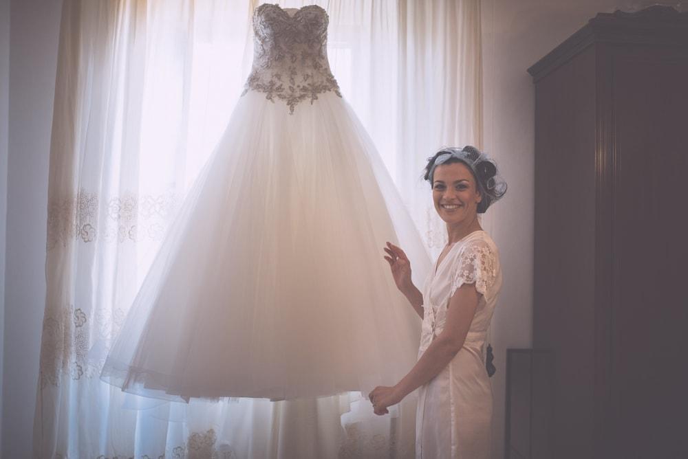 La sposa mostra il suo abito. Fotografo di matrimonio a Ischia di Castro, Viterbo e ricevimento a Manciano. Sposi Tiziano e Ladis. Noemi Federici, Fotografo Professionista di matrimonio a Viterbo, Tuscia, Ischia di Castro